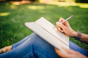 Photo of a woman writing outside